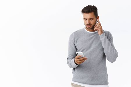 Good-looking guy getting ready leave office, put on wireless headphones, increase volume touch earphone, holding smartphone, looking mobile screen as changing earbuds settings, white background