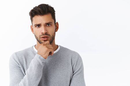Serious-looking concerned boyfriend listening friend got problem, trying figure out how help, standing white background, touching chin thoughtful, frowning as listening carefully to conversation