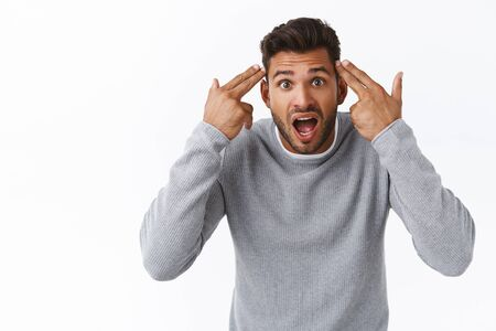 Annoyed and overreacting bothered handsome guy having argument with person making stupid dumb mistake, pointing temples and shouting at friend, quarreling