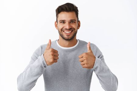 Smiling good-looking male friend give appreciation gesture, show thumbs-up and smiling in approval, agree everything excellent, like product, recommend