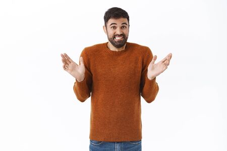 Portrait of awkward and clumsy cute bearded guy apologizing for making mess, raise hands sideways and shrugging indecisive, make confused smile, white background