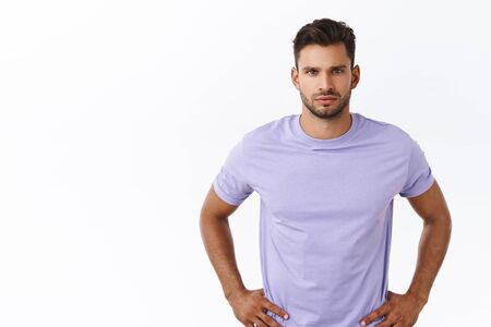 Waist-up shot, confident serious-looking young man with beard in purple t-shirt, hold hands on waist ready to act, listen carefully task, talking about business and office work, white background
