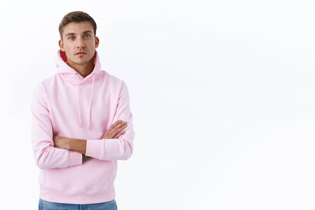 Portrait of carefree, relaxed handsome blond man in pink hoodie, cross arms over chest and look camera serious, getting straight to business, listening to information, standing white background Reklamní fotografie