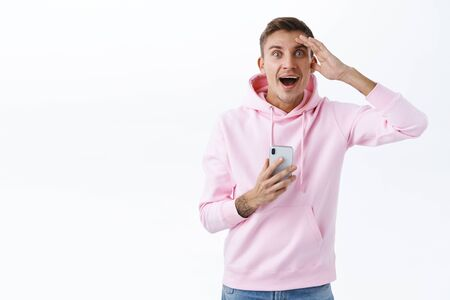 Happy, excited handsome man got great news or message, gasping astonished, look surprised and rejoicing, hold mobile phone, read awesome info, got applied job, employer called to congratulate