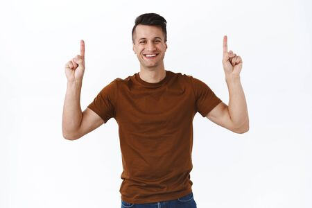 Cheerful good-looking caucasian man in brown t-shirt, advice click on top link, pointing fingers up and smiling, recommend upload app, go follow page or visit online store website, white background
