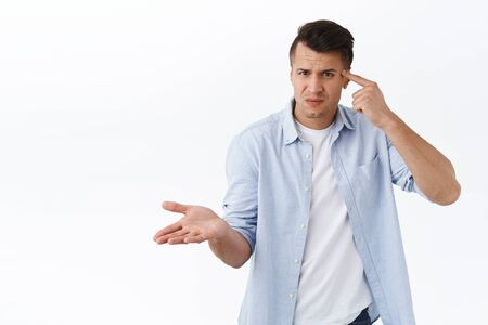 Portrait of frustrated and annoyed man hold finger against head and look perplexed, raise hand in dismay, scolding person being crazy, acting strange or stupid, white background