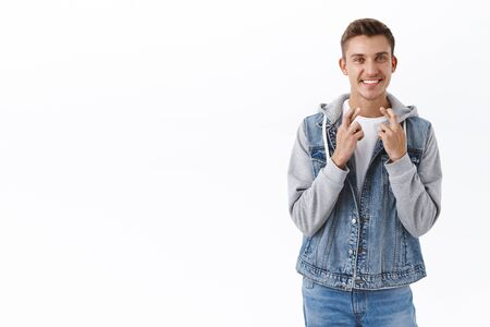 Portrait of hopeful, optimistic male student cross fingers good luck, beaming smile anticipate good news, relish positive result, awaiting for dream come true, making wish, white background