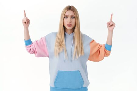 Worried, concerned blond caucasian girl pointing fingers up, frowning upset, consulting with you about bad troublesome situation, pointing fingers up, need help or opinion, white background