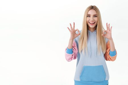 Excited cheerful blonde girl with beaming smile satisfied with good quality, show okay gesture laughing, recommend product, approve and like plan, standing upbeat white background