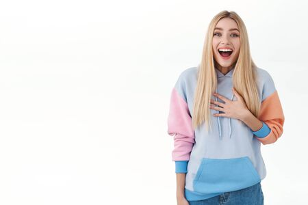 Portrait of surprised blond girl in hoodie look impressed and fascinated, touch chest and open mouth amused, smiling broadly astonished, receive great news, standing white background