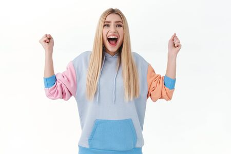 Happy, excited blonde girl in hoodie, chanting, celebrating victory, winning prize, achieve goal, raising hands up in hooray, smiling broadly, triumphing over white background Banco de Imagens