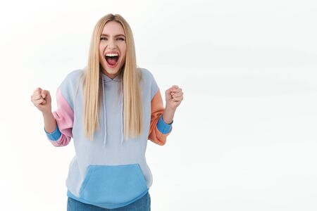 Portrait of enthusiastic attractive blonde girl in hoodie, chanting, scream yes and smiling, clench fists, celebrating victory, achieve goal, triumphing over win or receiving prize, white background