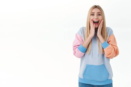 Rejoicing, happy feminine blond caucasian woman, sighing and smiling happy, touch cheeks and look camera with admiration and joy, standing white background, receive great news