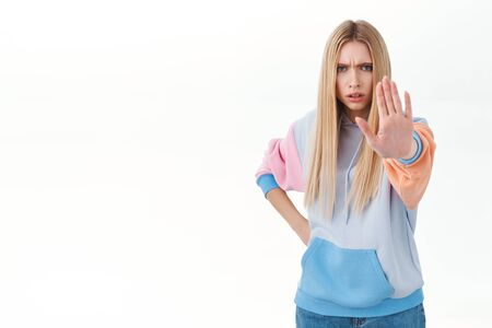 Mad blonde girl with long hair, colored hoodie, outward arm to camera, saying stop, prohibit action, warning someone disagree, trying to prevent bad thing happen, frowning serious, white background