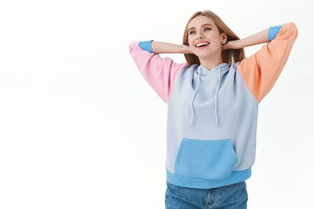 Upbeat good-looking relaxed blonde girl in hoodie, hold hands behind head and smiling broadly as looking away with peaceful chill face, vibing at home, enjoying self-quarantine time, white background