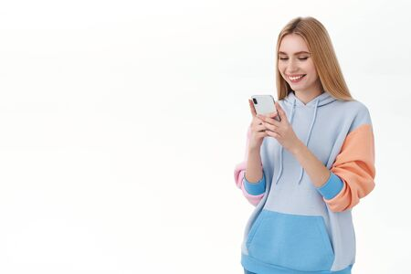 Communication, technology and online concept. Young happy blonde female student, feminine girl texting friend as found great internet store for shopping at quarantine, laughing mobile screen Banco de Imagens - 145883730