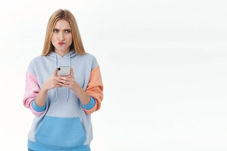 Communication, technology and online concept. Perplexed and thoughtful young blond girl thinking how to answer on risky text in dating app, biting lip, frowning look up, hold mobile phone