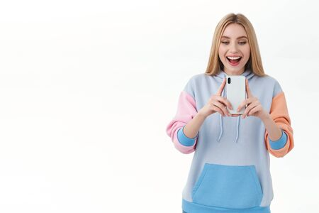 Communication, technology and online concept. Cheerful blonde girl taking photo of something amazing, record video on mobile phone as attend concert, smiling amused, white background