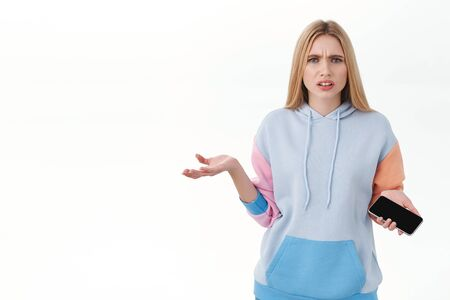 Communication, technology and online concept. Frustrated blond girl cant understand what happened, feel bothered and annoyed, shrugging with mobile phone in hand, grimacing disappointed Reklamní fotografie