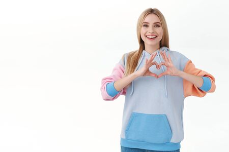 Cheerful attractive blonde female student in hoodie, showing heart sign and smiling, express love and tenderness, confess sympathy or passion, like someone, standing white background