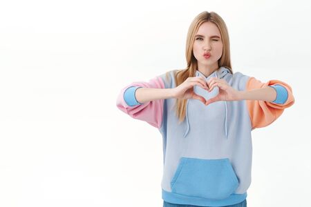 Portrait of silly, feminine blonde caucasian girl in hoodie, wink and making kiss face, showing heart sign, feel affection or sympathy, sassy confessing love, standing white background Banco de Imagens