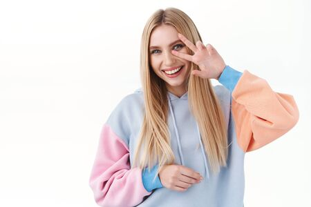 Beauty, lifestyle and fashion concept. Cheerful, kawaii blonde girl in hoodie, smiling silly and showing peace sign, express rejoice and happiness, positive emotions, white background
