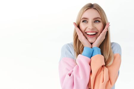 Beauty, lifestyle and fashion concept. Close-up portrait of dreamy, tender attractive blonde girl, touching her face and smiling as looking away at promo announcement, stand white background