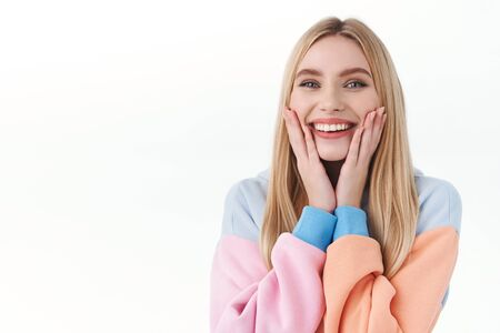 Beauty, lifestyle and fashion concept. Close-up portrait of cheerful, feminine blonde girl in hoodie, touching her cheeks and smiling, applied new cleansing product, feel soft tenderness of skin Banco de Imagens