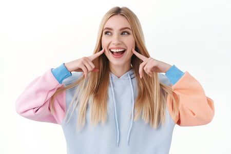 Beauty, lifestyle and fashion concept. Upbeat good-looking blond girl poking her cheeks and smiling, looking away with joyful, happy emotion, promote skincare cosmetics or makeup