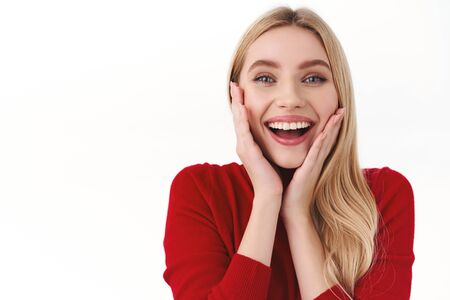 Beauty, women and fashion concept. Close-up portrait of amused, surprised blond girl receive incredible good news, touch cheeks and smiling amused, glad to win, triumphing, white background Reklamní fotografie