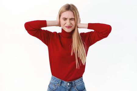 Work, career and lifestyle concept. Elegant blonde woman in red turtleneck, squinting and grimacing annoyed of loud neighbours, shut ears not hear noisy music, white background