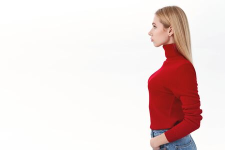 Work, career and lifestyle concept. Profile shot of confident good-looking blonde woman in red turtleneck, looking left with serious determined face, standing white background, waiting in line