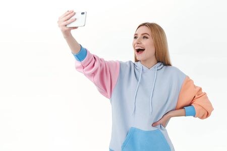 Communication, technology and online concept. Cheerful good-looking blonde female blogger, young girl taking selfie on smartphone, smiling, vlogging at home, record new content
