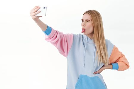Communication, technology and online concept. Silly attractive female vlogger, cute girl in hoodie, taking selfie on smartphone with extended arm, show tongue to phone camera, white background Banco de Imagens