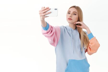 Feminine good-looking blonde girl with sensual expression, gently touching face as taking selfie on mobile phone, take photo herself feeling cute, using smartphone app filters, white background