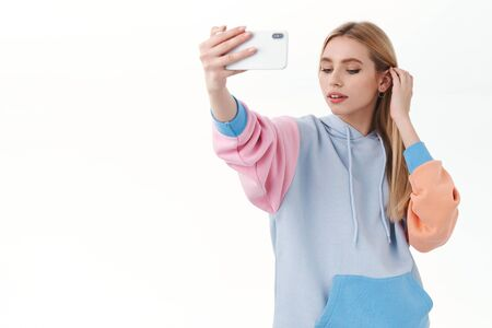 Portrait of tender, feminine, beautiful blonde girl, put hair strand behind ear, looking down sensual, taking selfie on smartphone, apply photo filter, using mobile app, standing white background