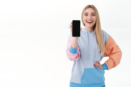 Communication, smartphone and promo concept. Happy attractive blonde girl in hoodie, advertise mobile application, showing cell screen, app on phone display, standing white background