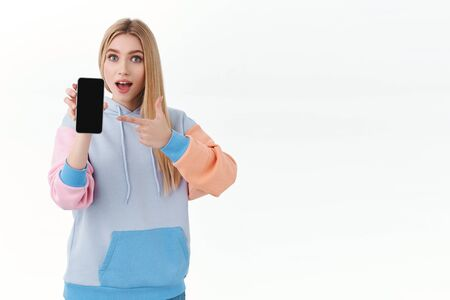 Communication, smartphone and promo concept. Surprised enthusiastic blond girl pointing finger at smartphone screen, recommend download application, showing mobile phone app or shopping site
