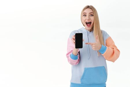 Communication, smartphone and promo concept. Excited happy, attractive blonde girl, cheering smiling broadly and screaming joyful, showing smartphone display, pointing at app on mobile screen