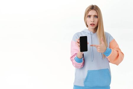 Communication, smartphone and promo concept. Portrait of frustrated blond girl being confused with strange bad news on media, pointing at mobile phone screen with worried expression Banco de Imagens