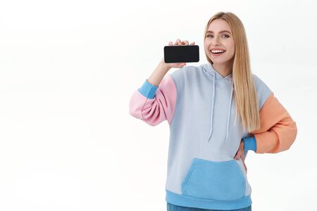 Communication, smartphone and promo concept. Confident happy, attractive woman promote mobile phone application or game, showing smartphone horizontally and smiling pleased