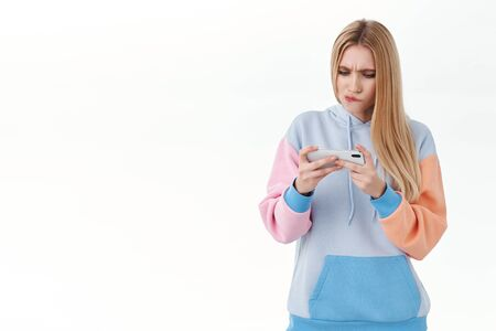 Serious-looking focused attractive blonde girl, download new racing game, holding mobile phone horizontally, pouting and frowning as trying to pass difficult level in online arcade, white background Banco de Imagens