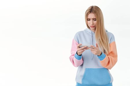 Upset, pensive blonde girl feel uneasy over failure, watching sad movie on mobile phone, sobbing and frowning distressed, holding mobile phone horizontally, standing disappointed white background