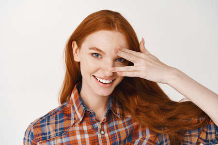 Close-up of beautiful redhead lady with blue eyes and pale skin, smiling at camera, standing over white background