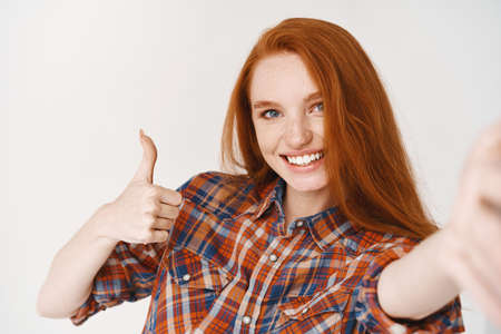 Beautiful redhead girl smiling happy and showing thumb-up while taking selfie on smartphone, front camera view, white background Banque d'images