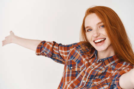 Beautiful and happy girl with ginger hair introduce something via video call, holding smartphone and extending hand to demonstrate product, taking selfie with object