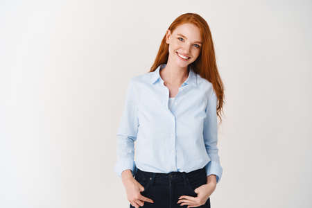 Young professional woman in office shirt smiling at camera. Redhead female manager looking happy, standing over white background Imagens