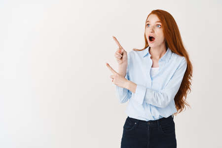Amazed redhead female manager pointing and looking at upper left corner in awe, standing impressed against white background Standard-Bild