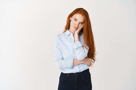 Image of beautiful girl student in blue shirt looking annoyed or bored, leaning face on palm and sulking at camera, white background