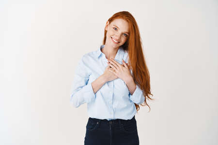 Young woman manager with red hair and pale skin, holding hands on heart and thanking you, being grateful, expressing gratitude while standing over white background